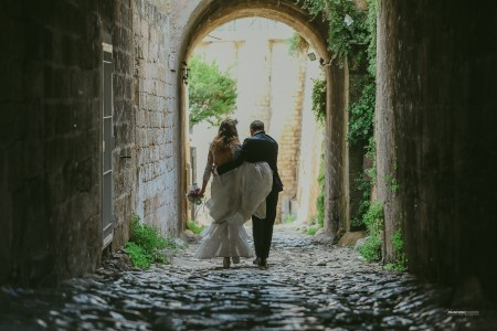Bride and groom embraced on the avenue under the arch
